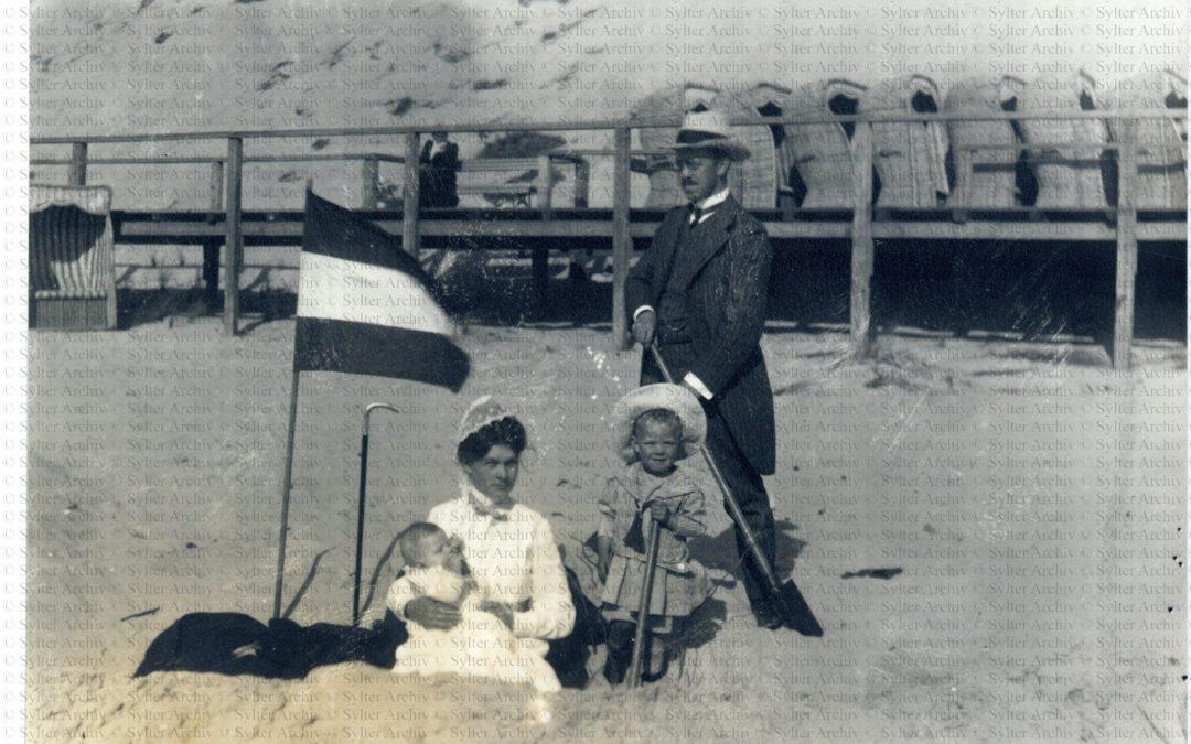 Familienbild am Strand mit Hut und Stock